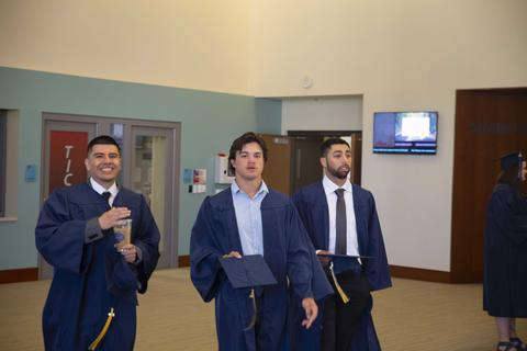 Three male graduates walk through Shaw Lobby in their gowns holding their caps.