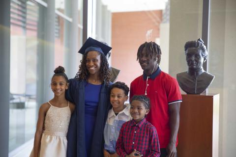 Female graduate in her cap pose with her family inside the lobby windows of Shaw Center.