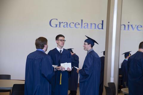 Three male graduates, two in gowns and on in cap and gown, visit with each other in Shaw Lobby.