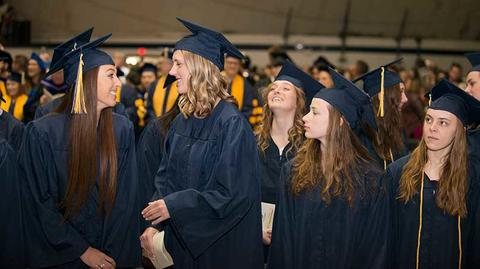 Four female graduates in their cap and gown laugh together standing at their seats during the commencement ceremony in Closson