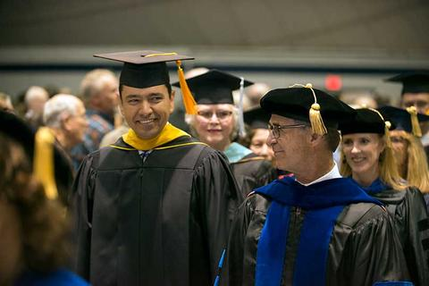 The two male commencement speakers in regalia walk the aisle to the stage.