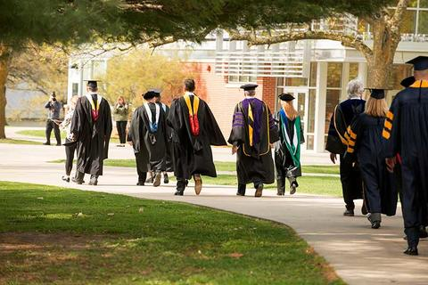 Faculty in regalia walk the sidewalk on campus to the Closson for the commencement ceremony