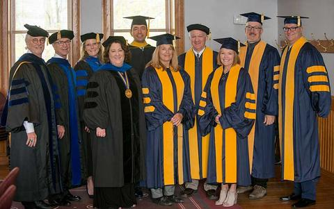 The university president with board of trustees president, alumni board president and other faculty and guest speakers pose in regalia at commencement