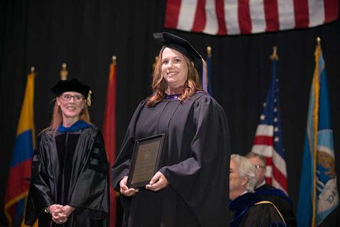 Faculty member Julia Franklin poses on stage in her regalia at commencement with her award she just received from Jill Rhea, VPAA