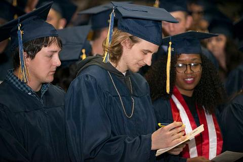 Three graduates, two male and one female, read through the commencement program during the commencement ceremony in Closson