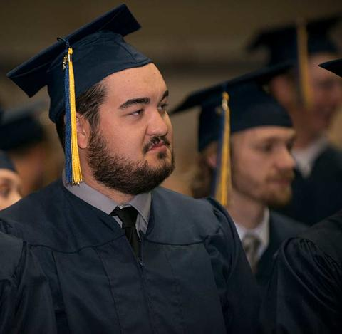 Male graduate in cap and gown with tassel attends his commencement ceremony in Closson.
