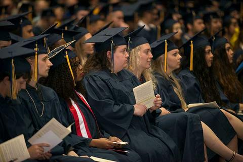 Group of graduate in their regalia sit in a row of seats during the commencement ceremony in Closson