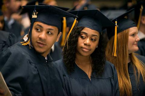 One male and one female graduate in cap and gown sit in their seats during commencement in Closson glancing to the side to spot family in the audience.