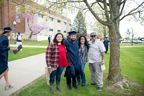 Graduating senior, Phillip, poses in regalia outside Closson with his family.