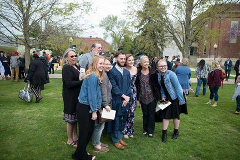 Male graduate poses in his gown outside Closson following commencement with a large group of his family members that attended the ceremony.