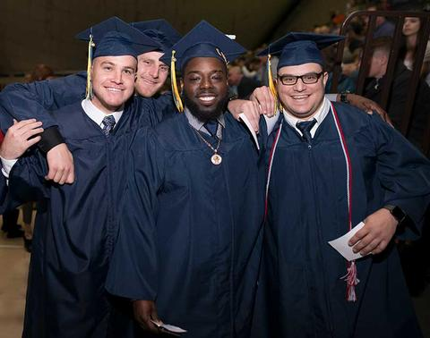 Four male graduates in full regalia pose together in Closson at the commencement ceremony.