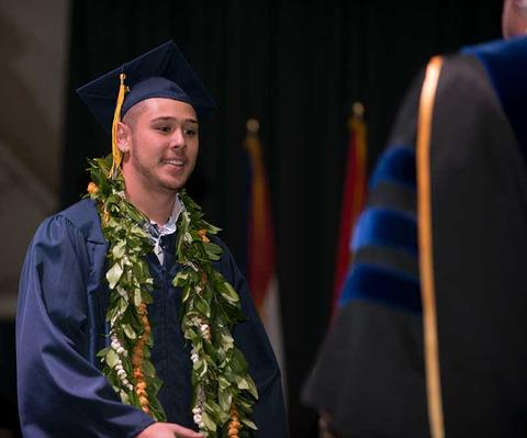 Male graduate in cap and gown with leafy lei and tassels approaches to receive his diploma on stage at commencement in Closson.