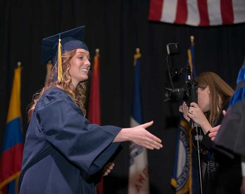 Female graduate in cap and gown on stage at commencement extending her hand to shake as receiving diploma.