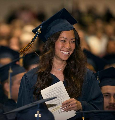 Lexus Lovan at graduation in Closson in her cap and gown holding a commencement program and smiling big.