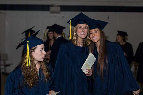 Three female graduates in regalia pose in Closson together at commencement.