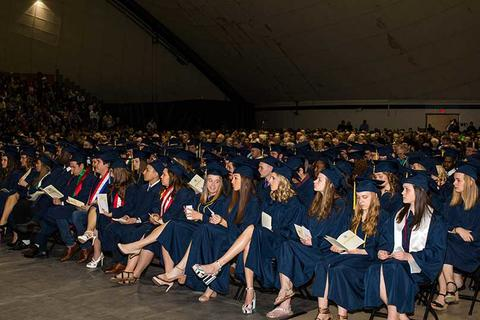 Front row of graduating students in cap and gown sit during the commencement ceremony in Closson.