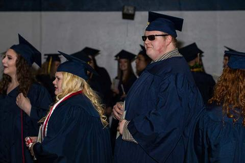 Mle graduate in sunglasses, cap and gown and female graduate in her regalia waiting in line with other graduates to file into their seat for commencement in Closson