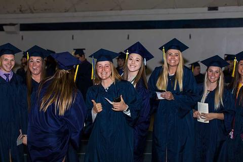 One male and seven female graduates, one facing away from the camera, pose in line together in their cap and gown waiting to file into seats in Closson at commencement.