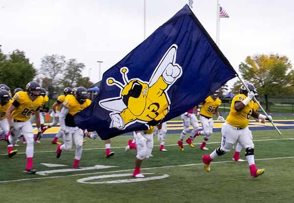 Football team runs on the field waving Yellowjackets flag