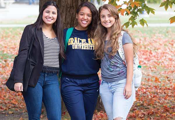 Three girls huddle together to pose under a tree in the Quad on the Lamoni campus.