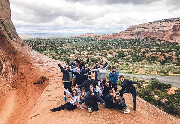 Group of students pose atop a dessert cliff in the Southwest