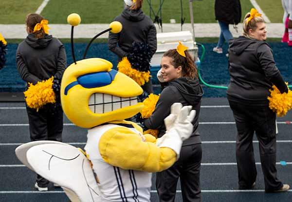 Sting with cheerleaders on the football field during a game