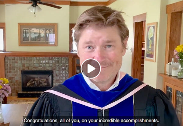 Dean of the College of Liberal Arts and Sciences Brian White shown in a paused moment of the graduation video