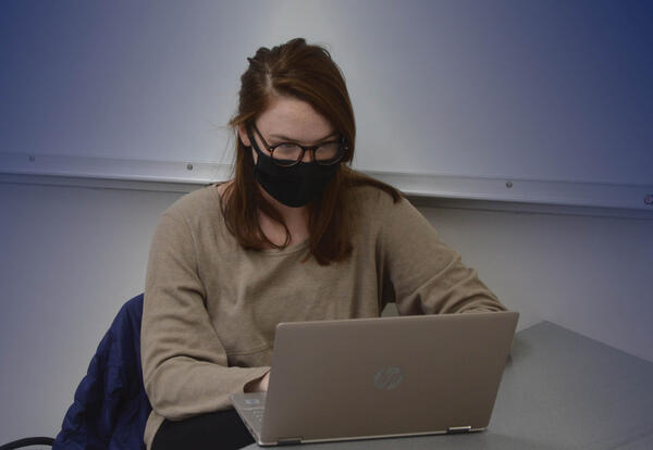 Student in mask working on laptop