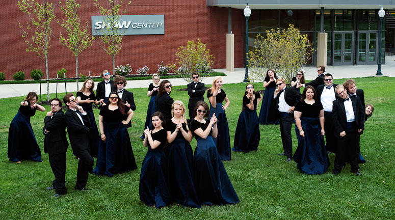 Chamber singers posing in front of Shaw in their formal attire