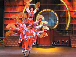 Chinese Dragon Acrobats in costume, stacked on a single bicycle, waving Chinese fans