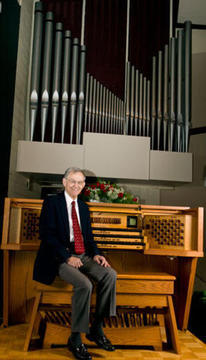 Oliver Houston sitting on the bench in front of the pipe organ