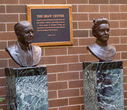 Bronze busts of Francis and Lottie Shaw on marble pedestals in front of a brown brick wall with a plaque in between