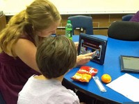 Female Graceland student sitting at a classroom table, working with a male child from the local community. on a tablet.