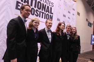 Group of students on stage at Enactus competition