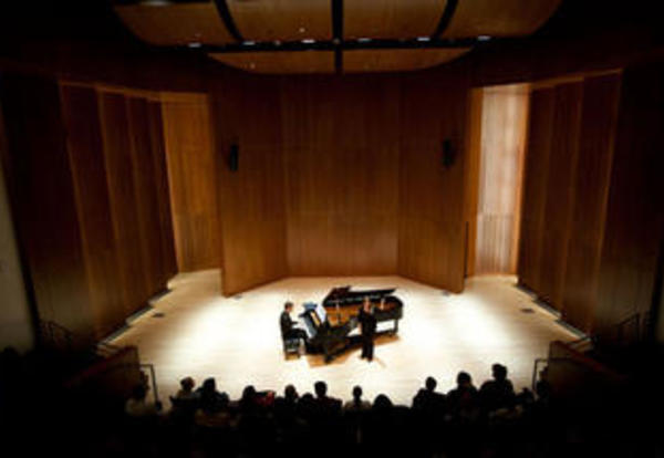 A pianist performing before an audience in Carol Hall