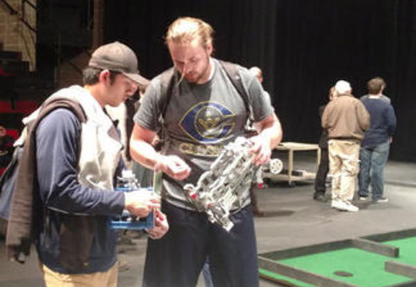 Two male Graceland students inspecting their robot at the Robotics Competition