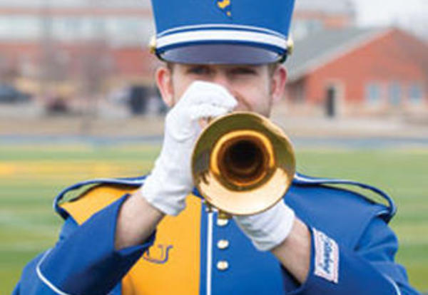 Male marching band student in uniform playing his horn