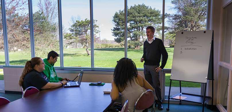 Professor Dan Platt instructs students at an executive table