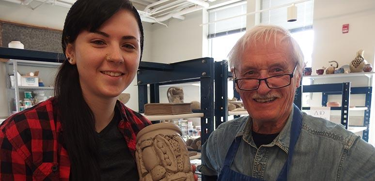 Male professor and female student pose in the ceramics studio