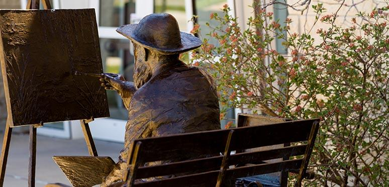 A bronze statue of an older male artist sitting on a park bench painting on canvas held by an easel outside the entrance of a building