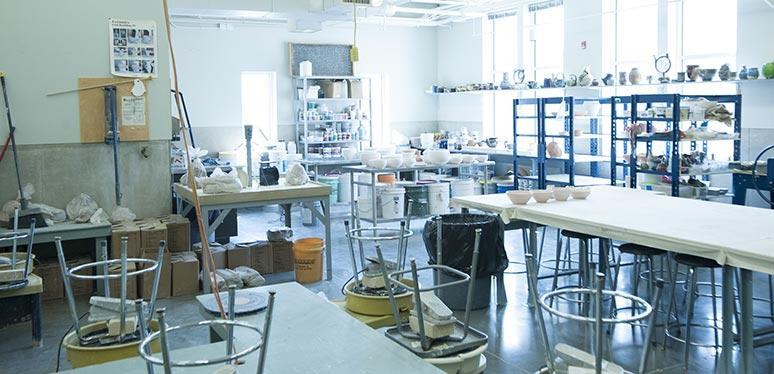 A ceramic studio with all art materials neatly placed on shelving and stools turned upside down on top of tables