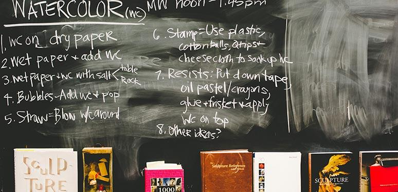 A chalkboard at the front of a classroom covered in chalked writing with several books placed along the base of it