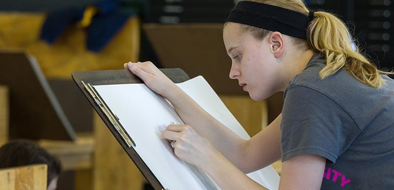 Female caucasian art student draws against an easel holding paper