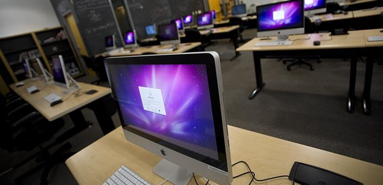An open and lit-screened Mac laptop on a table in a Mac lab
