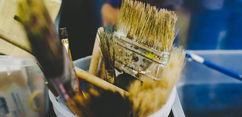 Several used paint brushes of different sizes and types stick straight up out of a small bucket