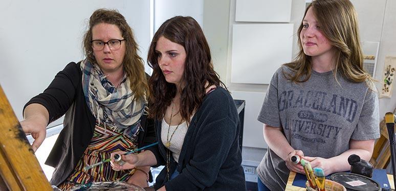 Karen teaching female art students on easel