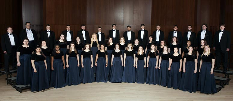 Concert Choir group of male and female singers in their formal attire posing on stage