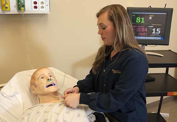Female nursing student in lab practicing on a patient simulation mannequin