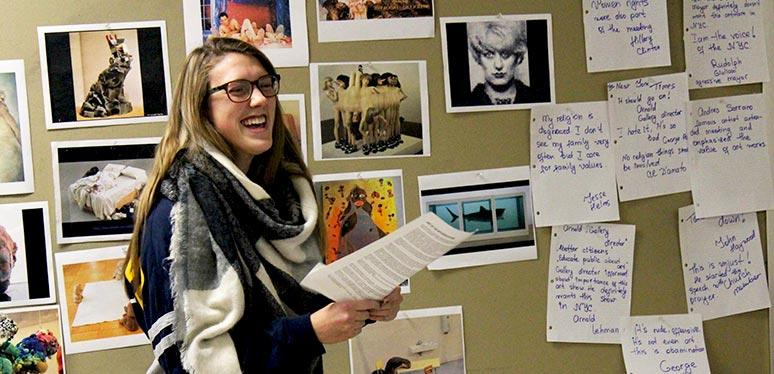 Female caucasian student laughing in front of a bulletin board with photocopied art, in color, attached to it at the front of a classroom