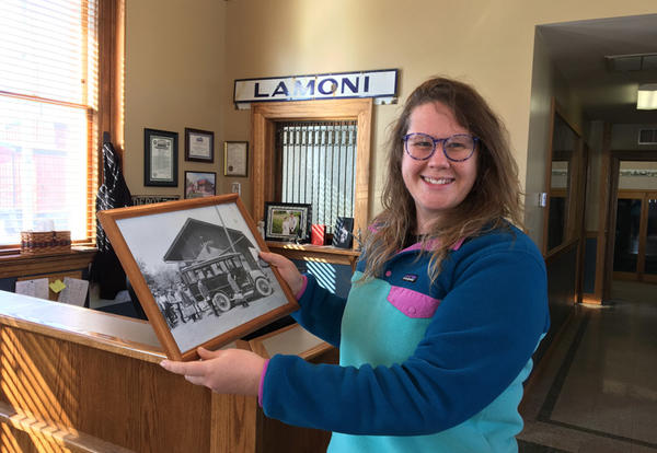 Assistant Professor of Art Karen Gergely at City Hall holding a framed black and white photo of the old filling station in town